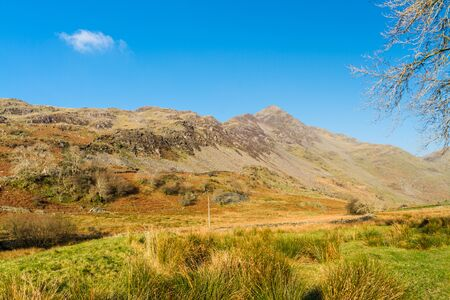 Beautiful Day in Winter Autumn Fall and copyspace in blue sky. Cwm Croesor Valley and mountain Cnicht, Snowdonia national Park, Gwynedd, Wales, UK, Landscape Фото со стока