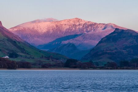 Last sun of the day on snow covered Snowdon Mountain. Landscape with Nantlle Lake in foreground. Фото со стока