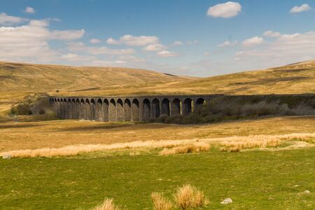 Ribblehead Viaduct, landscape with hills behind.