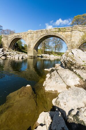Looking up at Devils Bridge, over the River Lune. Kirkby Lonsdale, Cumbria, England, portrait, wide angle. Фото со стока