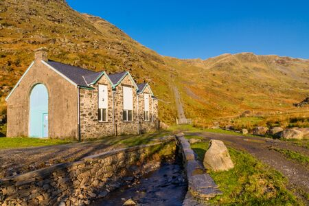 Beautiful Day in Winter Autumn Fall and copyspace in blue sky. Blaen y Cwm hydro electric power station Head of Cwm Croesor Valley and mountain Cnicht, Snowdonia national Park, Gwynedd, Wales, UK, Landscape Фото со стока