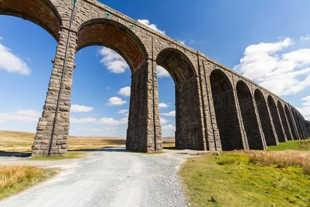 Sunny day with path up to to the sunlit arches of the Ribblehead Viaduct, landscape. North Yorkshire, Europe, England, landscape. Фото со стока