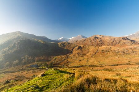 Winter or Autumn Fall Snowdonia landscape. Peak of Mount Snowdon with snow on it. Landscape, wide angle.