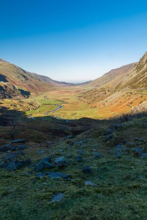 Morning sun on valley, Nant Ffrancon Pass, Snowdonia national Park, Gwynedd, Wales, UK. Portrait, copyspace at top.