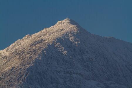 Snow on the Peak of Mount Snowdon, North Wales, landscape, telephoto zoom. Фото со стока