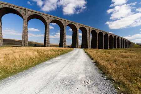 Sunny day with path up to to the sunlit arches of the Ribblehead Viaduct, landscape. North Yorkshire, Europe, England, landscape and wide angle. Фото со стока