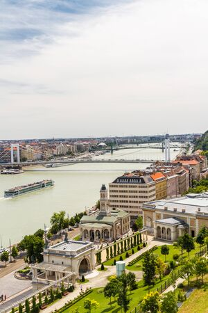 River Danube looking South in Budapest Hungary with ferries, the Elizabeth Bridge and Gelert Hill, wide, angle, wideangle, portrait. Stock fotó