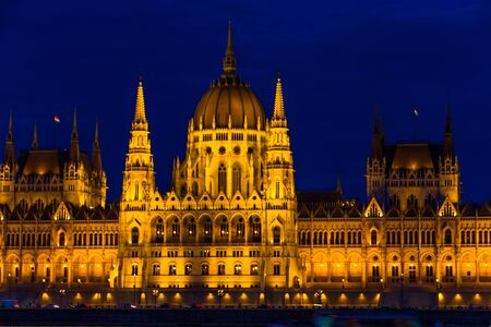 Night light on the flood lit Hungarian Parliament Building, landscape River Danube in foreground, at angle.