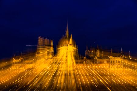 Zoom effect blur on Night light on the flood lit Hungarian Parliament Building, landscape, wide angle.