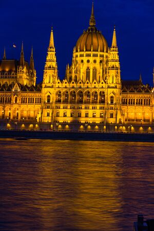 Night light on the flood lit Hungarian Parliament Building, portrait River Danube in foreground, at angle, copyspace at bottom.