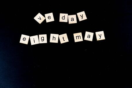 Children wood blocks lettering, jumbled scattered VE Day 2020 on black background, copyspace below. Reklamní fotografie