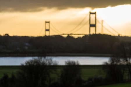 Morning light behind the Severn Crossing suspension bridge across the River Severn landscape, blur blurred.