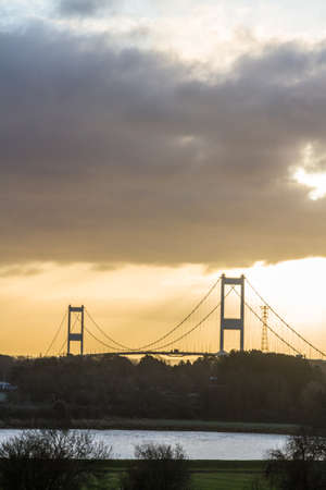 Morning light behind the Severn Crossing suspension bridge across the River Severn portrait copyspace at top. Фото со стока