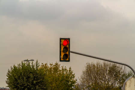Traffic light on red, cloudy sky copyspace at top, landscape. Фото со стока