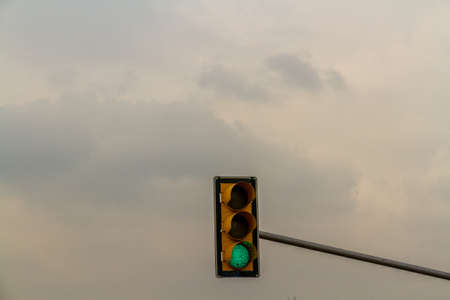 Traffic light on green, cloudy sky copyspace at top, landscape.