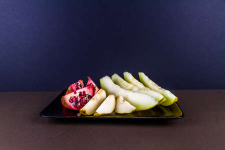 pomegranate melon and pear sliced and arranged on plate landscape. dark background, copyspace at top