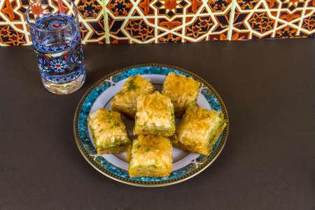 Turkish Baklava baclava piled on plate, Moorish tile background, landscape.