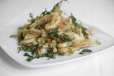 A specialty from Sicily. Fried prawns with arugula. White background.