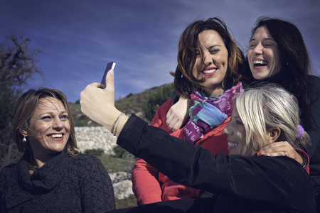 Four women friends are doing a selfie. Nature background. Stock Photo