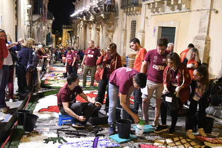 NOTO, ITALY - MAY 19th 2018: The famous Infiorata, in Noto, the town in Sicily famous for its baroque. Artists associations are creating drawings with flowers and petals in the gorgeous Via Nicolaci. Archivio Fotografico - 107121402