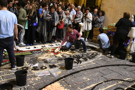 NOTO, ITALY - MAY 19th 2018: The famous Infiorata, in Noto, the town in Sicily famous for its baroque. Artists associations are creating drawings with flowers and petals in the gorgeous Via Nicolaci. Archivio Fotografico - 107121405