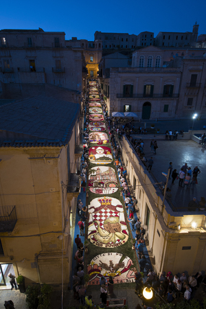 Noto, Italy - May 20, 2017: the infiorata of Noto dedicated to Principality of Monaco seen from San Carlos tower. Noto, famous for baroque, is a Unesco Site. Archivio Fotografico - 107121538