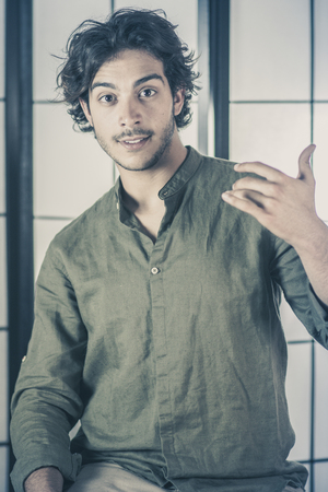An handsome young man, 20Y, is posing in studio with raised hands at chest with interrogative expression. Green skirt. Retroilluminated booths in the background. Archivio Fotografico - 104596685