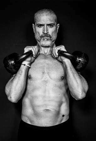 A man 50 Y is holding is raising weights. Black background. Black and white. Archivio Fotografico - 104616781
