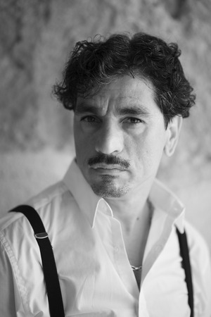 Portrait of a man with an interesting face typical of southern Italy, that can be defined both handsome or ugly, with black hair, moustaches, white skirt, braces, leaning to a wall. Archivio Fotografico - 109761135
