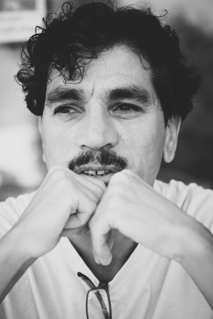 Portrait of a man with an interesting face typical of southern Italy, that can be defined both handsome or ugly, with black hair, moustaches, white skirt. Standard-Bild