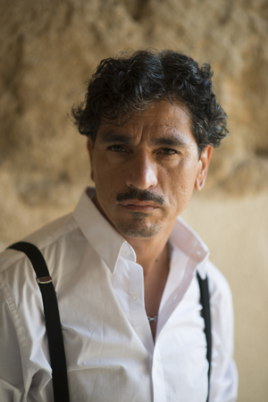 Portrait of a man with an interesting face typical of southern Italy, that can be defined both handsome or ugly, with black hair, moustaches, white skirt, braces, leaning to a wall. Archivio Fotografico - 109761142