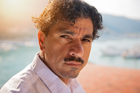 Portrait of a man with an interesting face typical of southern Italy, that can be defined both handsome or ugly, with black hair, moustaches, white skirt, braces, leaning to a wall.