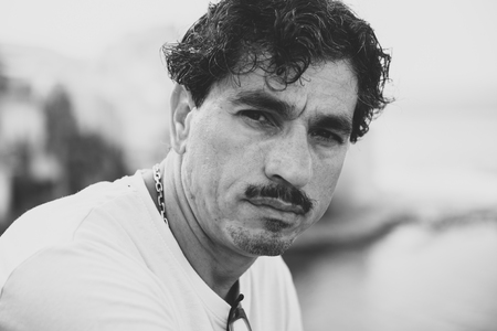 Portrait of a man with an interesting face typical of southern Italy, that can be defined both handsome or ugly, with black hair, moustaches, white skirt. Archivio Fotografico - 109761150