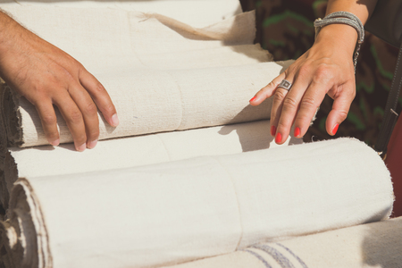 Female hands are touching rolls of linen cloth a the market, valuating the purchase.