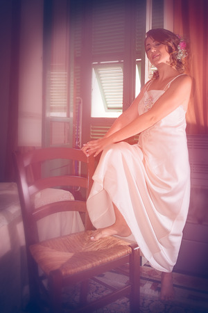 A girl, on the day of her wedding, white dressed, is holding a foot on a chair. Archivio Fotografico - 117309665