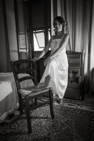 A girl, on the day of her wedding, white dressed, is holding a foot on a chair.