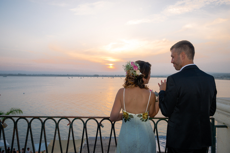 A young couple on the day of their wedding is posing at sunset lying on a balcony over the port of Siracusa, in Sicily. Archivio Fotografico - 117309679