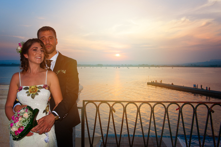 A young couple on the day of their wedding is posing at sunset lying on a balcony over the port of Siracusa, in Sicily.