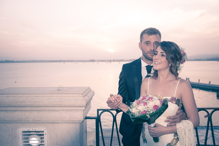 A young couple on the day of their wedding is posing at sunset lying on a balcony over the port of Siracusa, in Sicily. Archivio Fotografico - 117309681