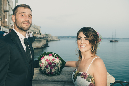 A young couple on the day of their wedding is posing at sunset lying on a balcony over the port of Siracusa, in Sicily. Archivio Fotografico - 117309685