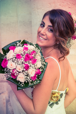 A girl, on the day of her wedding, white dressed, is posing . On the background, the doric column of Siracusas Cathedral, in Sicily. Standard-Bild