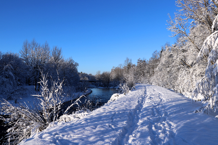 The river and a coast under snow with glitter sky
