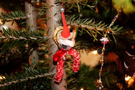 The small plastic figure caught on the christmas tree as decoration Stock Photo