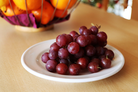 The red grapes on the white plate and in the background there are fruits in the bowl Stock Photo