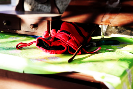 A red work gloves on the wooden table covered by color tablecloth