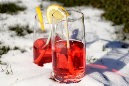 A strawberry juice in small glass on the snow hill for chilling and ready for drunk. Add lemon for design Banque d'images