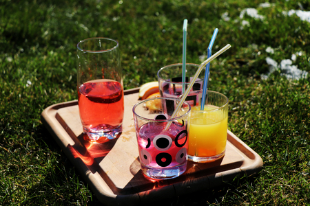 A strawberry, lemon and orange juices in the garden for house party. It is ready for drunk.