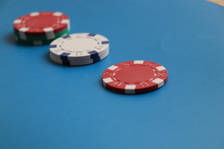 A few colorful token lying on the blue background. They are using in roullete and hazard Stok Fotoğraf - 100583175
