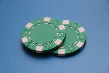A two green tokens for playing roullete or some poker on the blue background Stok Fotoğraf
