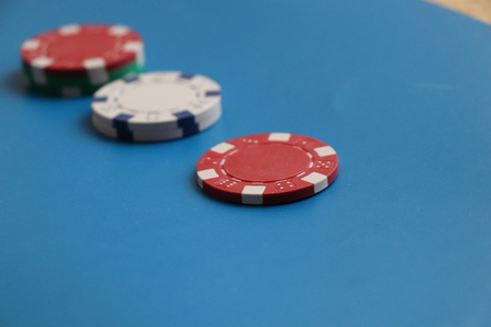 A beautiful red token for gambling on the blue background and play in roulette